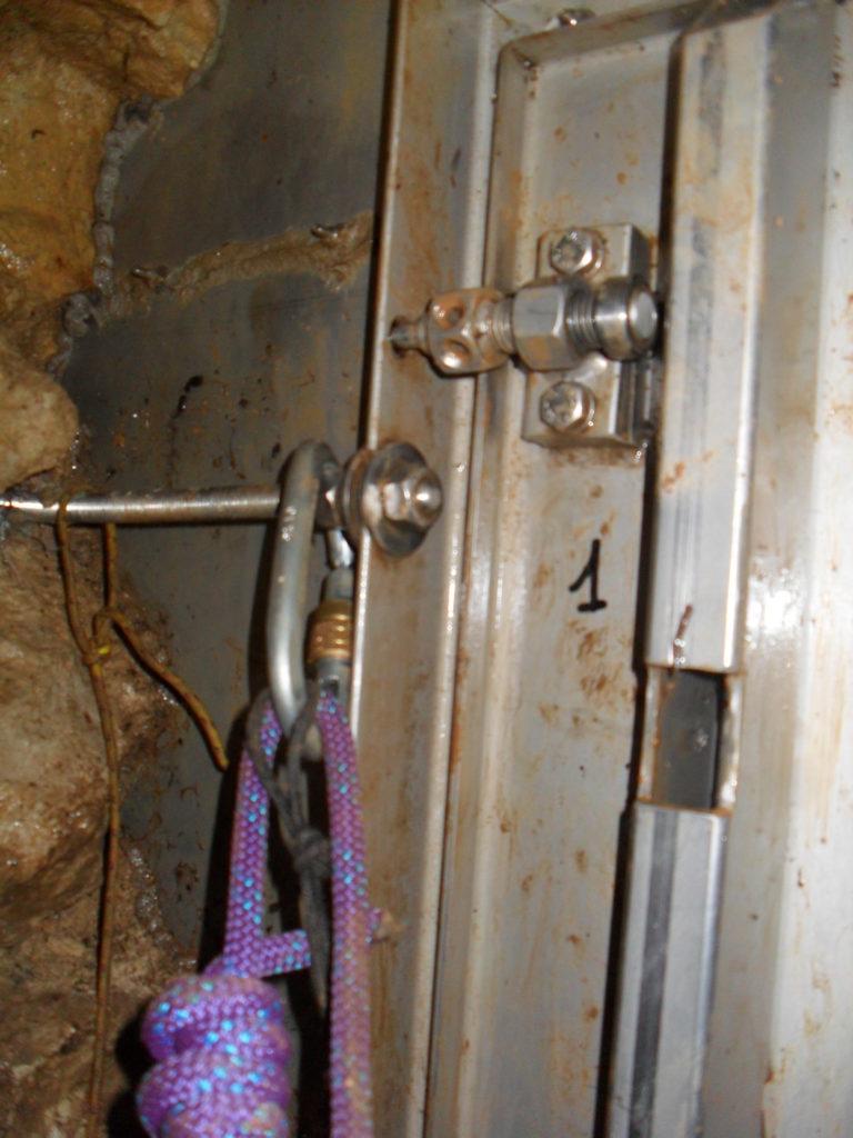 Nella parte superiore si vede il dettaglio della vite di chiusura della porta: bisogna svitare il cilindro dalla testa liscia